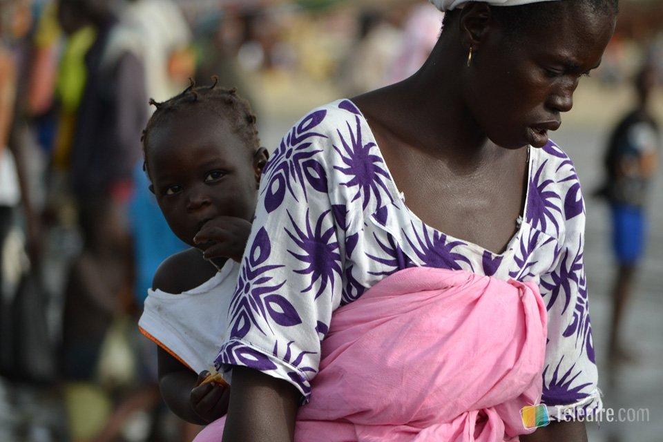 Las gambianas suelen llevar a los niños en la espalda