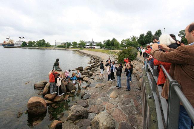 Turistas junto a la sirenita en Dinamarca
