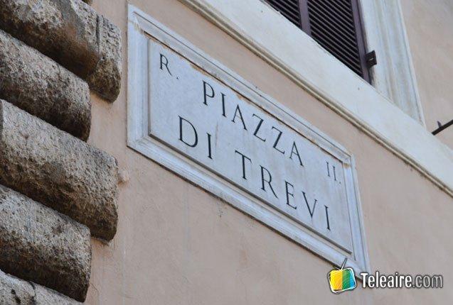 cartel de la piazza di trevi junto a la fontana